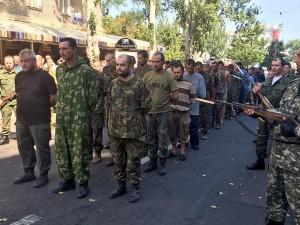 В Донецке в окружении вооруженных ополченцев провели колонну украинских военнопленных, а также выставили на обозрение разбитую украинскую военную технику.